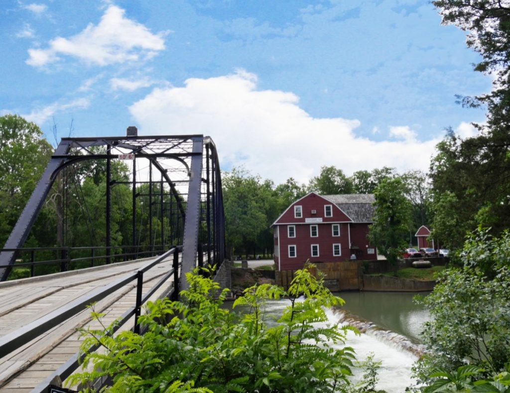 a photo of a red house and War Eagle bridge, which is nearby Cave Springs, Arkansas