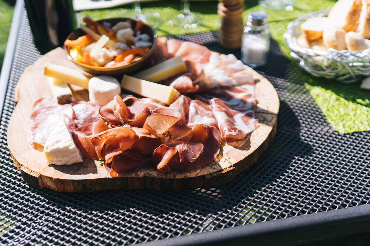 View of charcuterie board in the sunshine containing cheese and Italian meats