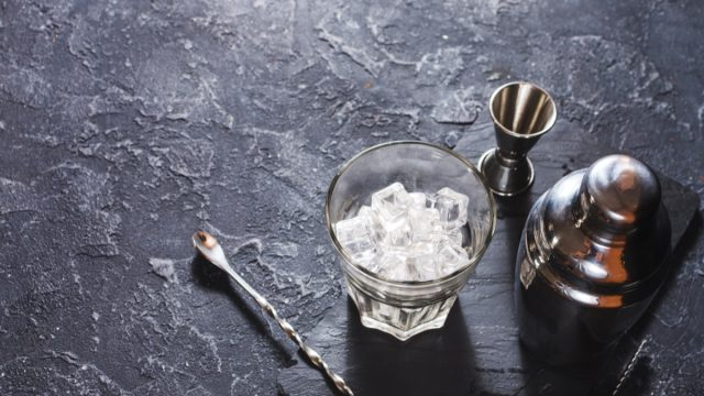 set of cocktail making tools on slate background