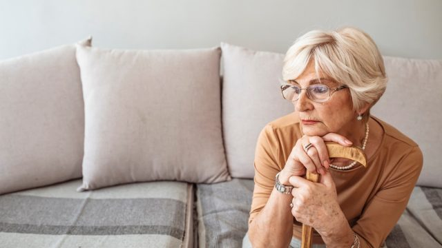Senior woman holding a walking stick. Elder lady sitting on the couch with wooden walking stick. Retired woman with her wooden walking stick at home