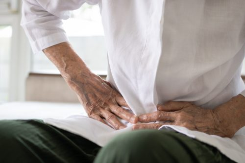 Sick senior patient having aching belly,hands hold stomach,stomachache,old people with symptoms gastrointestinal system disease,crampy abdominal pain hurt in stomach caused by indigestion or diarrhoea