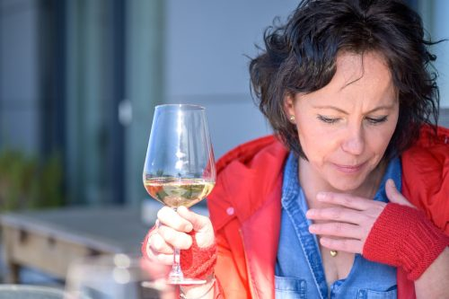 Woman coughing holding her hand to her chest with respiratory distress as she enjoys a glass of wine outdoors in a concept of symptoms of the coronavirus or Covid-19
