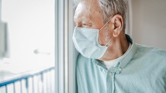 A senior man is at home by the window, he is wearing a protective face