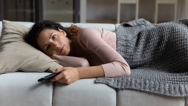 Tired millennial female relax at home after hard work day switch on favorite series