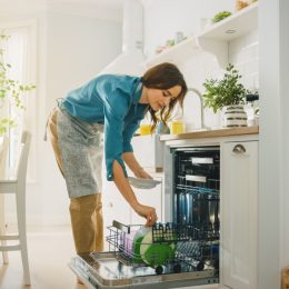 Woman loading a dishwasher without pre-rinsing dishes before