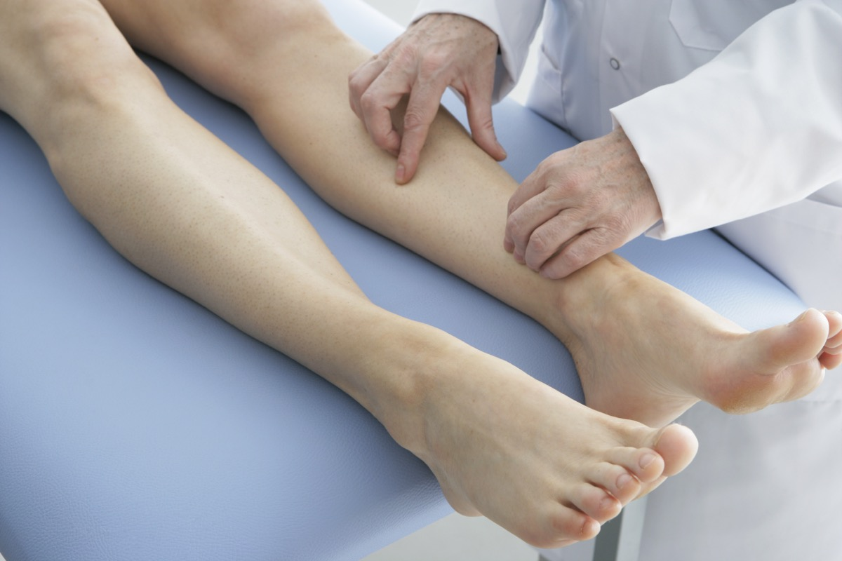 doctor examining patient's legs on table