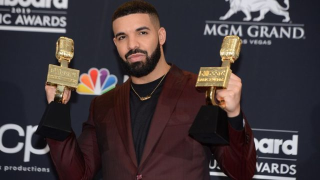 Rappe Drake holding award statues during a ceremony