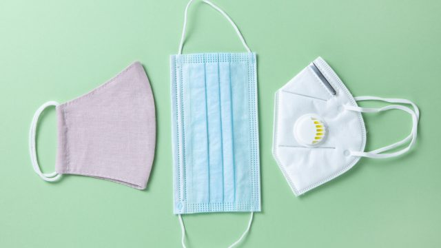 A cloth mask, surgical mask, and N95 respirator sitting on a green background