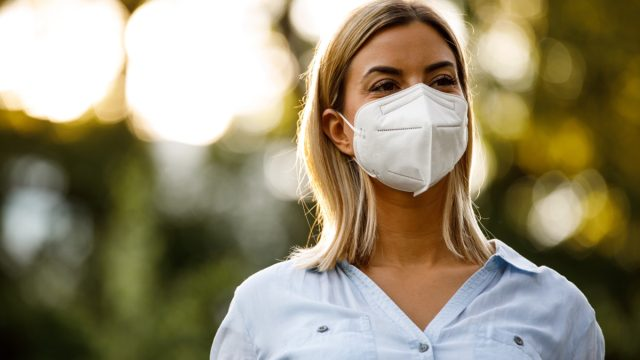 Copy space shot of happy young woman standing at the public park, enjoying a beautiful day out. She is smiling behind N95 face mask she is wearing and contemplating.