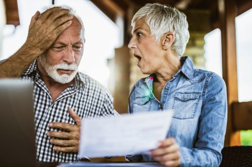 Shocked senior couple reading their home finances in disbelief at balcony.