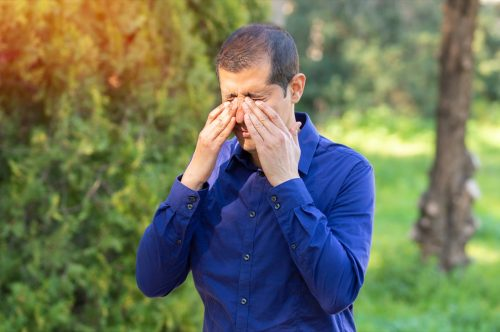 Man covering eyes with hand from sunlight
