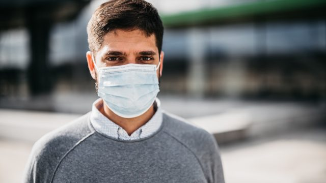 One young businessman with protective face mask standing outdoors in front of his office building.