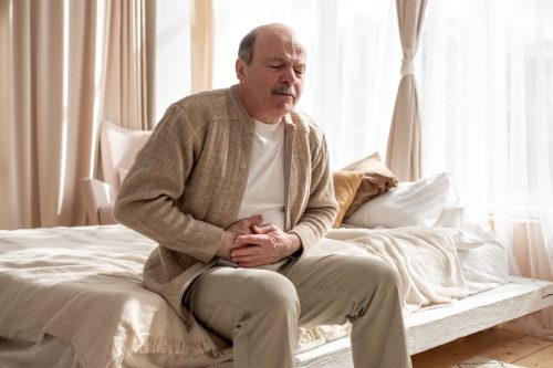 Senior man having stomach pain sitting at home. Nausea or belly pain.