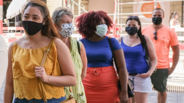 People of multi generation wearing face mask and standing in a queue