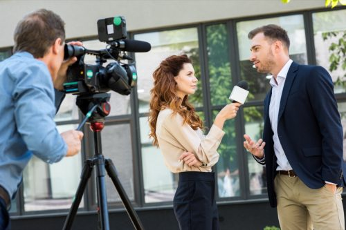 A camera man filming a journalist who's interviewing