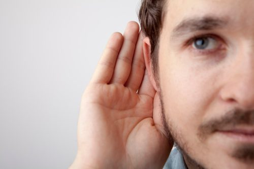 man. cupping his ear, listening