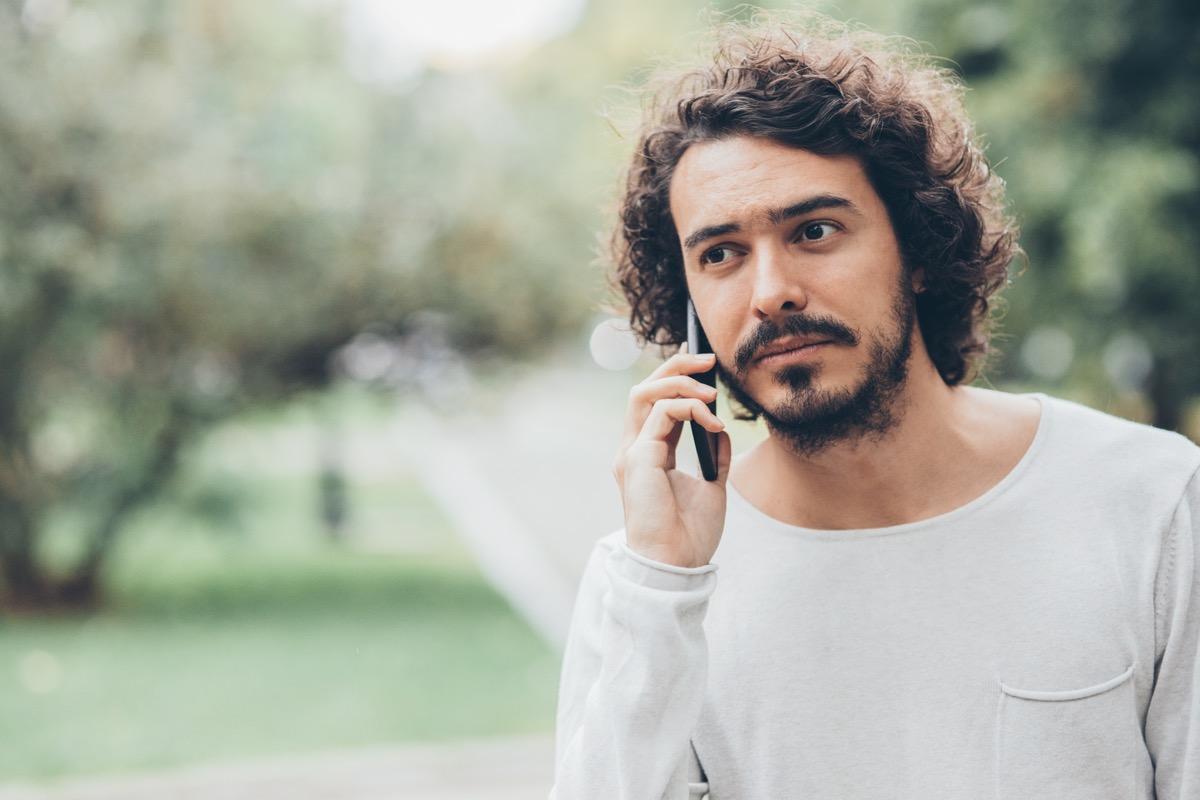 Man making a phone call outdoors.