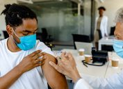 A young man receiving a COVID-19 vaccine or booster from a healthcare worker
