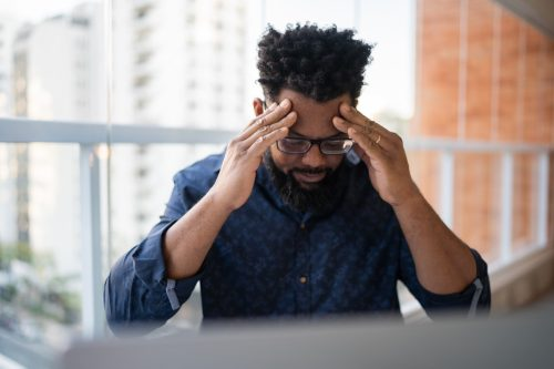 Worried man working with headache at home