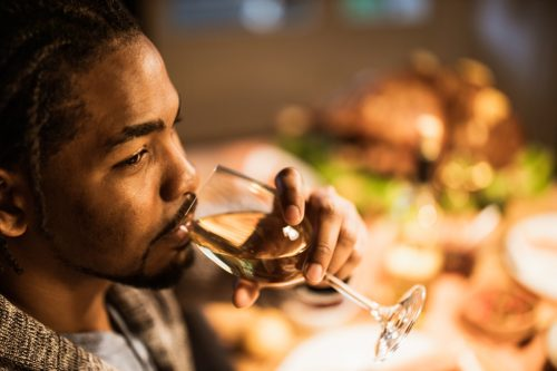 man enjoying while drinking wine at home and looking away.