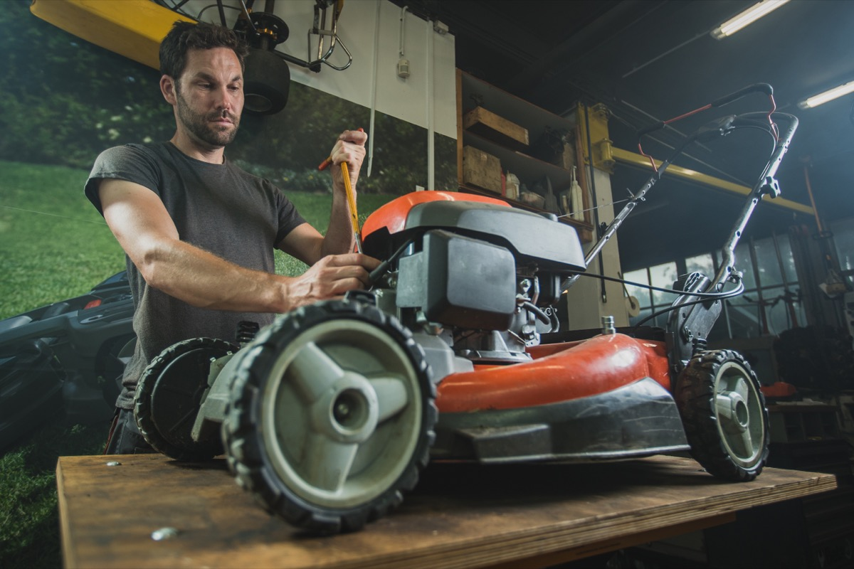 man fixing lawn mower in garage