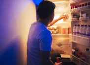 Man is opening the refrigerator to get a soft drink during the night
