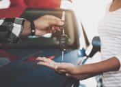 Man giving a woman car keys at a dealership