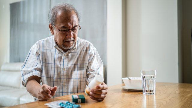 older man looking at bottles of prescription medication on wooden table