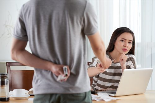 Unrecognizable man giving part of his salary to pretty young wife and hiding remains behind his back, interior of living room on background