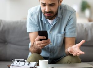 A man looking at his phone with a frustrated and confused look on his face, likely because it doesn't work
