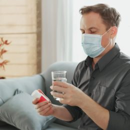 man looking at pill bottle while wearing surgical mask indoors
