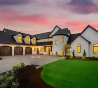mansion with green yard and three car garage with glowing interior lights and sunset sky
