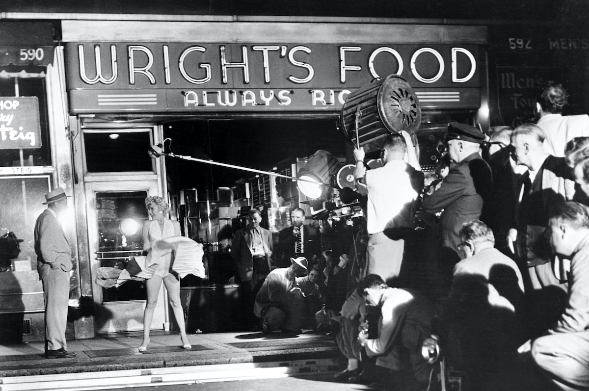 """Scene outside a food store at 51st Street and Lexington Avenue early today as Marilyn Monroe stood over a subway grating and had her skirts blown up by a giant blower while talking to Tom Ewell in a scene from the movie they're making of the famed stage play """"Seven Year Itch."""""""