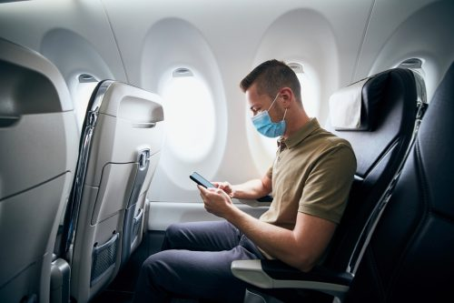 Man wearing face mask and using phone inside airplane during flight. Themes new normal, coronavirus and personal protection.