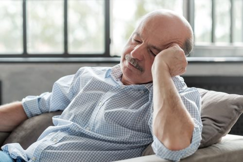 man sleeping on couch, taking afternoon nap at the living room
