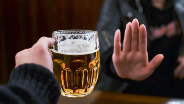 person holding out hand to indicate they don't want a glass of beer