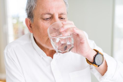 Handsome senior man drinking a fresh glass of water at home