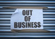 paper out of business sign on metal store grate
