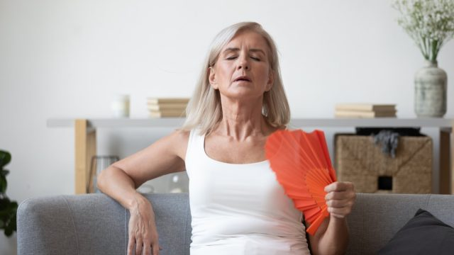 Unwell elderly female retiree sit on couch feel dehydrated tired of heat use hand waver to cool down, overheated stressed elderly woman suffer from heatstroke in living room with no air conditioner