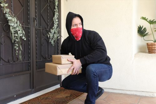 Man stealing packages off porch