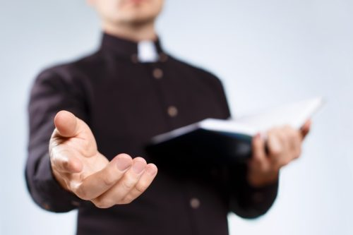 Priest with his hand out and holding a bible