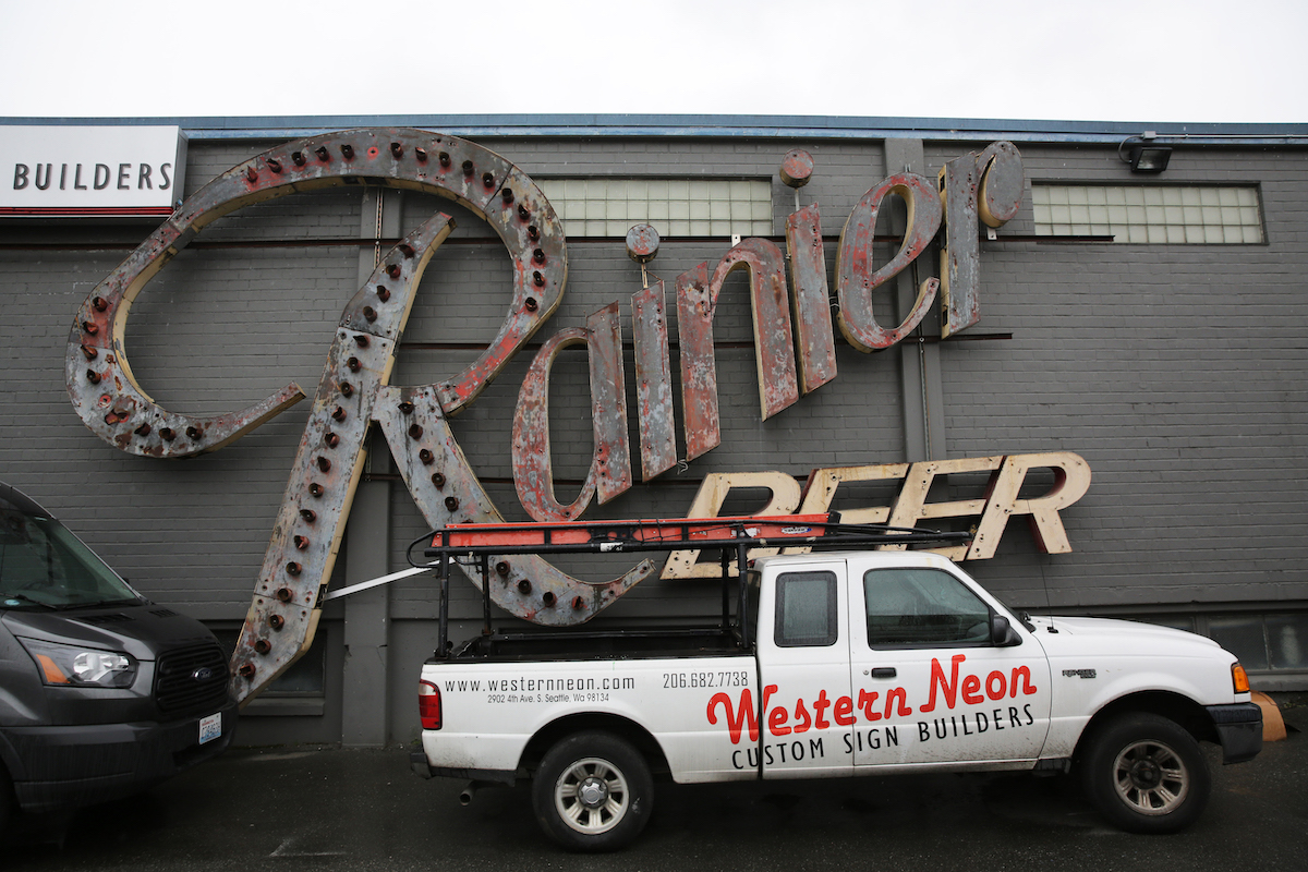 An original Rainier Beer sign hangs on an exterior wall of the Western Neon shop in Sodo.