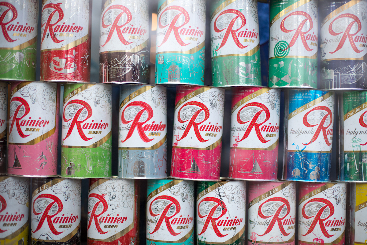 Display of vintage Rainier Beer cans, in an antique food background