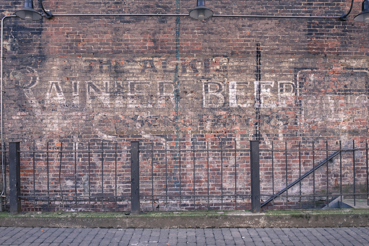 An old Historic Alki Rainier Beer advertising sign on a brick wall in Occidental park in the historic Pioneer Square neighborhood.