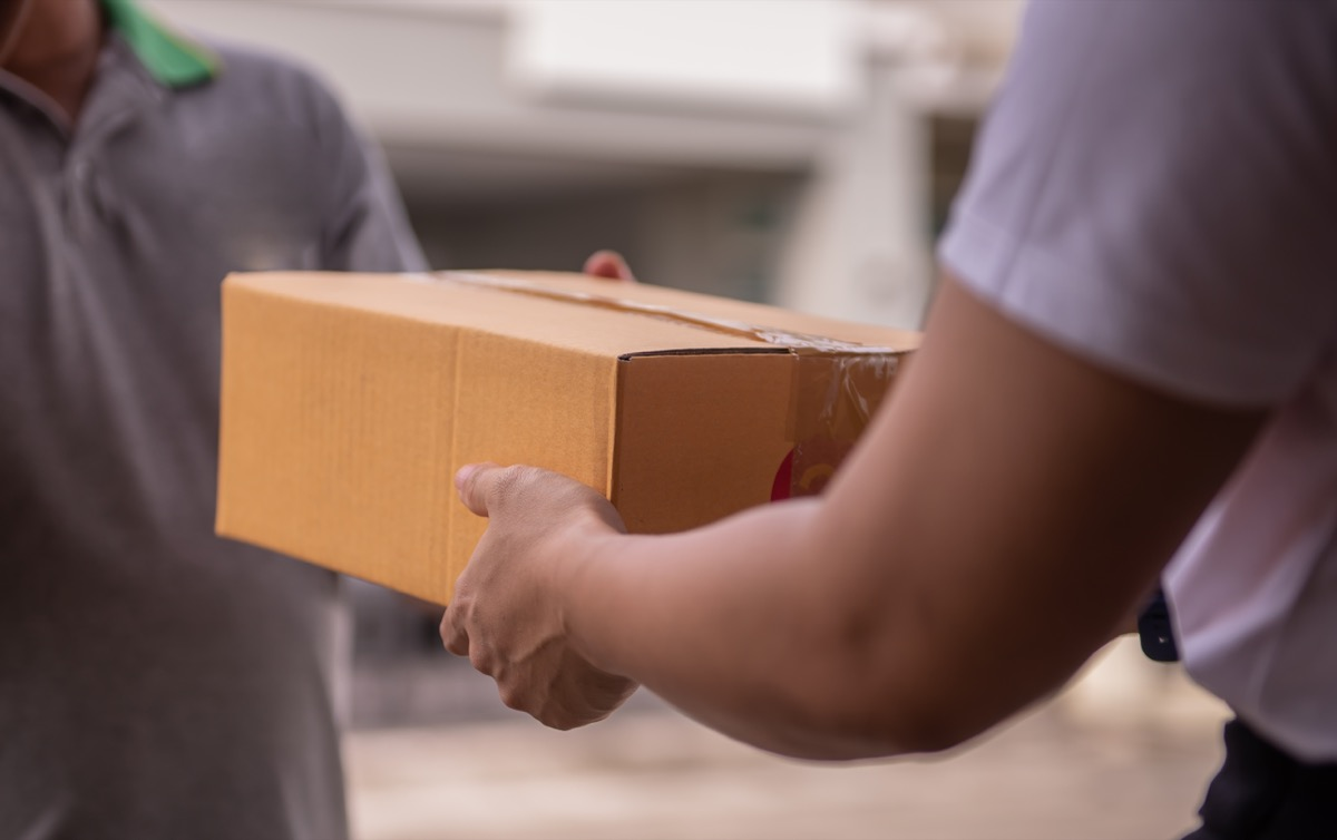 man handing cardboard box to person at postal office