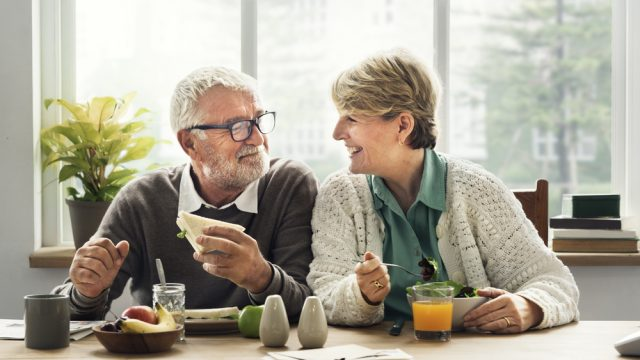 A senior couple sitting at the table eating breakfast