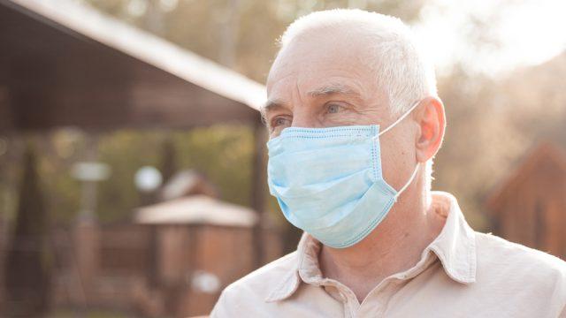 A senior man wearing a face mask outdoors