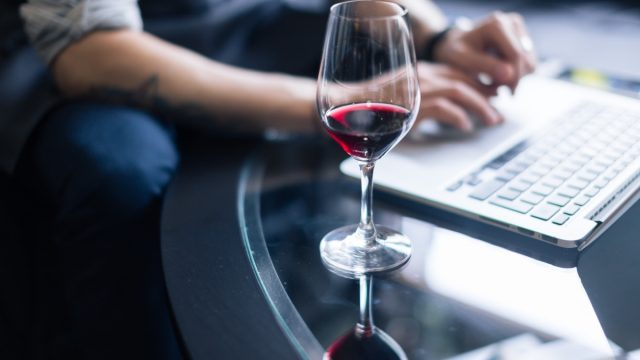 woman shopping on laptop while drinking wine