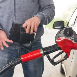 Person pumping gas with an empty wallet
