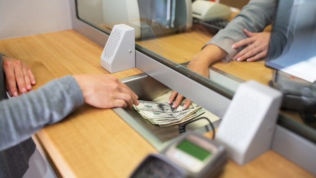 Person withdrawing money from bank teller